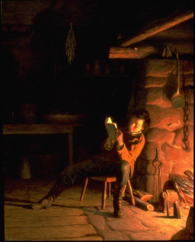 A figure wearing dark boots, dark pants, and brown overshirt reads, sitting on stool with his back to lit fireplace. Set in darkened domestic interior, table and drying herbs visible at back, wooden floorboards and stone of fireplace are illuminated. (Larson 2/5/18)